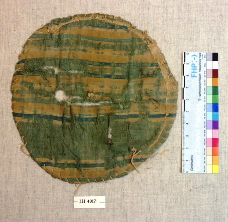Tattered circle of fabric with horizontal green and yellow stripes
