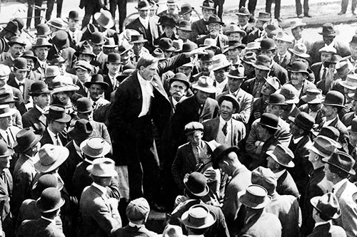 black and white photo of a crowd ofmen in suits and hats