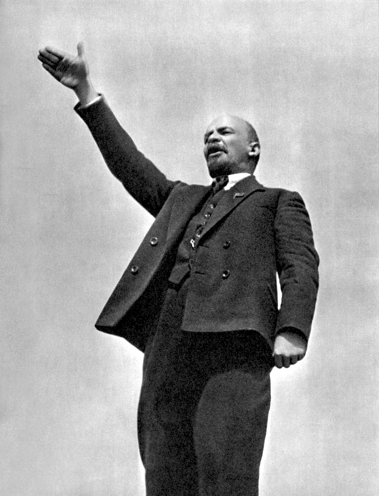 Photograph of Lenin standing, facing to the left with his right arm raised