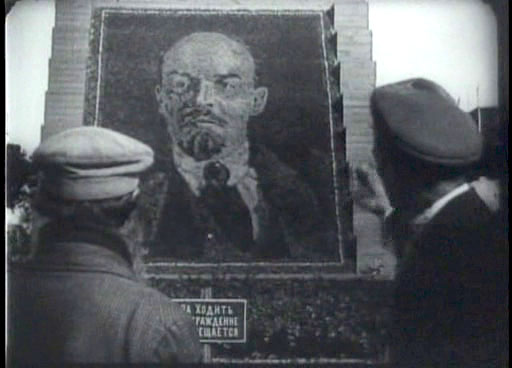 Two men regarding an image of Lenin