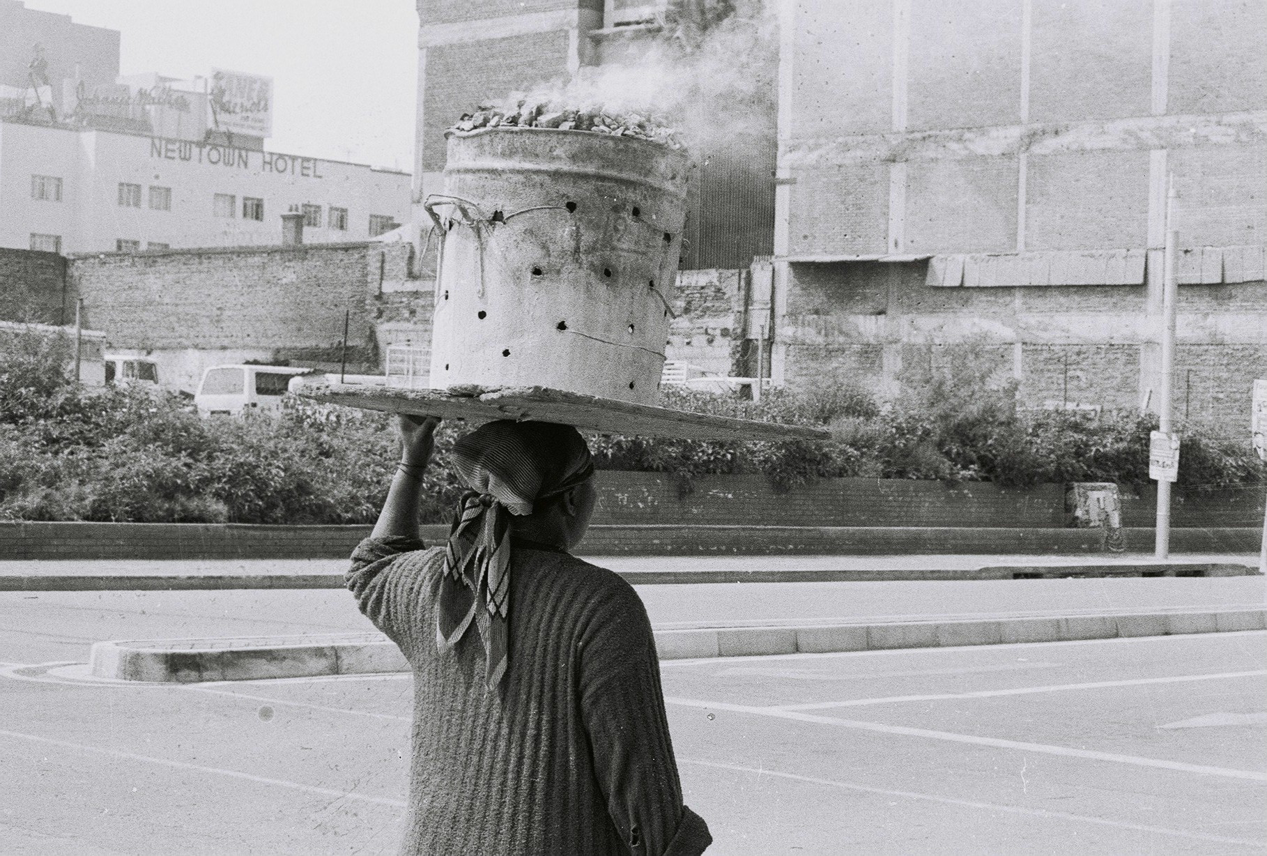 black and white photograph of a woman carrying a bucket of hot coals on her head, seen from the back