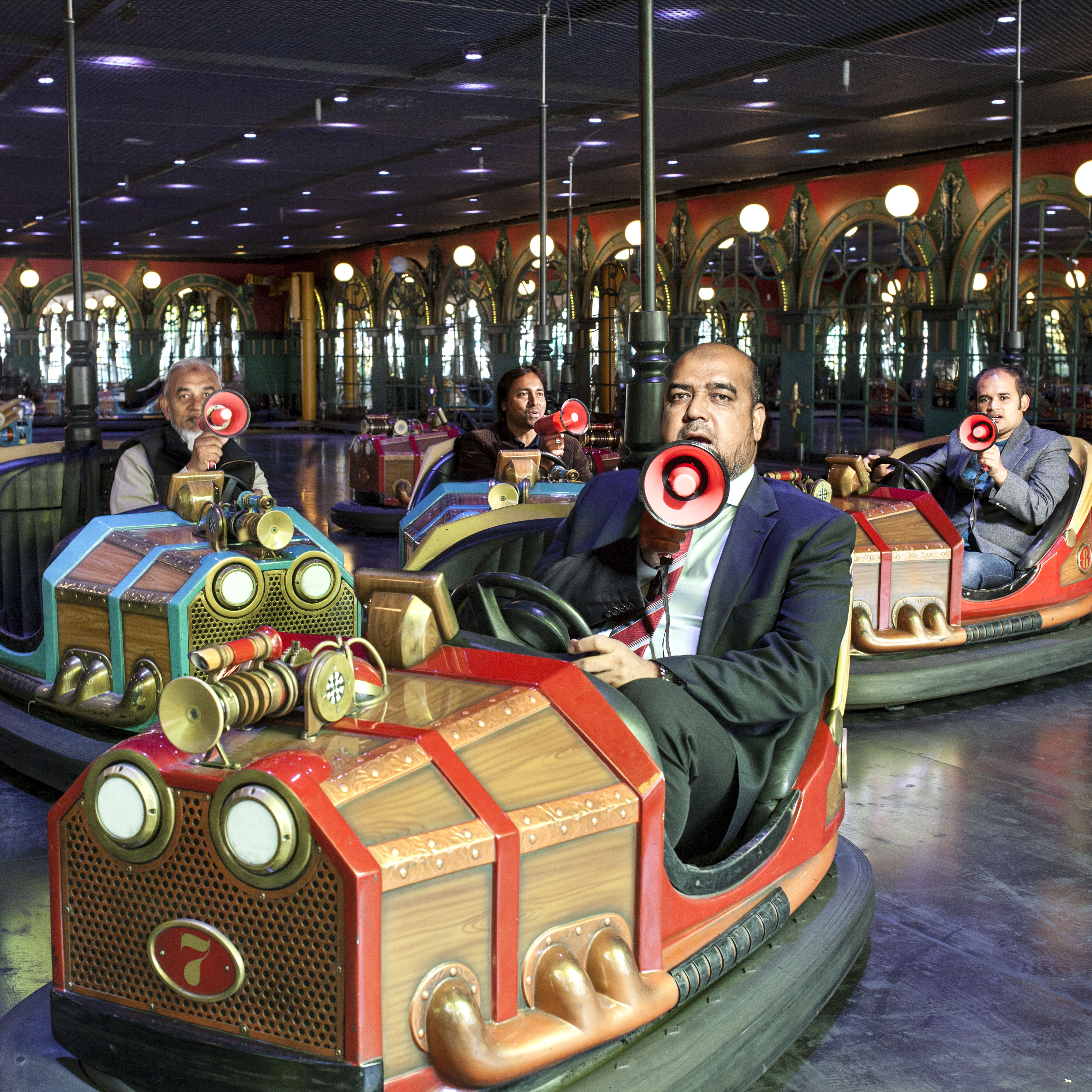 Immigrant men shouting into megaphones and sitting in bumper cars