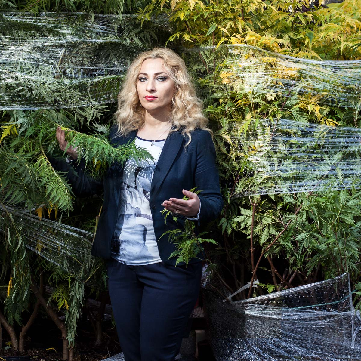 Blond immigrant woman standing in bushes